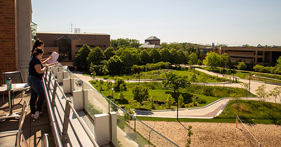 Two researchers observe and record site use on the University of Michigan North Campus